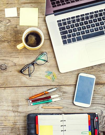 Office desk wth laptop, pens, iPhone, calendar and coffee mug