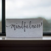 "Photo of a card on a windowsill that says ""mindfulness"""