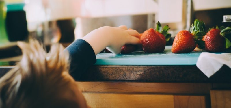 Childhood weight comments might stop this young child from reaching up to pluck a gorgeous red strawberry from the blue cutting board on the kitchen counter, as seen in this photo.
