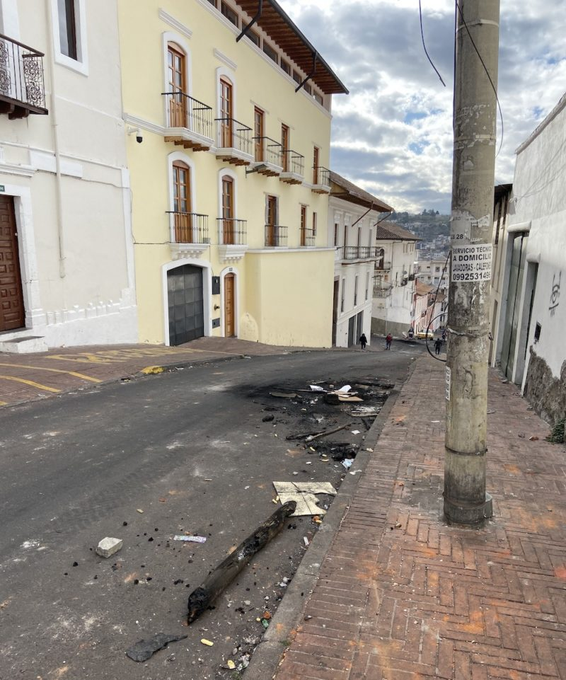 Photo of a street in Quito, Ecuador with remnants of burned wood and debris from the previous night's protests laying in the street.